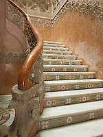 Mosaic tiles of flowers and leaves lead the way up the grand staircase, which is further adorned with sprouting stone flowers and an ornately carved marble handrail