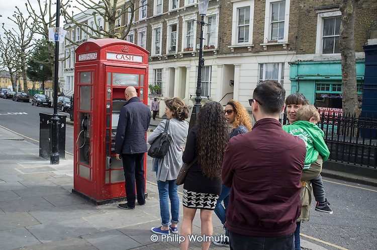 Queue for an ATM cash machine in a telephone box close to Portobello Road street market, London.