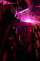 A welder at work in a fabricating shop.