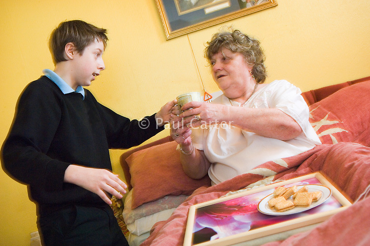 Young carers looking after elderly relatives.  Photo posed by models.  Model released...Young boy in school uniform brings a tray of tea and biscuits to his bed bound grandmother / elderly / disabled relative...Following info from http://www.barnardos.org.uk :  .With so many adult responsibilities, young carers often miss out on opportunities that other children have to play and learn. Many struggle educationally and are often bullied for being 'odd'. They can become isolated, with no relief from the pressures at home, and no chance to enjoy a normal childhood. They are afraid to ask for help as they fear letting the family down or being taken into care..Facts and figures.othe average age of a young carer is 12..othe 2001 census shows that there are 175,000 young carers in the UK, 13,000 of whom care for more than 50 hours a week..omore than half of young carers live in one-parent families and almost a third care for someone with mental health problems.
