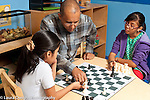 Afterschool chess program for elementary students graduates of Headstart program male teacher working with two 5th grade girls