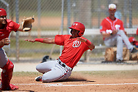 Washington Nationals Juan Soto (25) slides home during a minor league Spring Training game against the St. Louis Cardinals on March 27, 2017 at the Roger Dean Stadium Complex in Jupiter, Florida.  (Mike Janes/Four Seam Images)