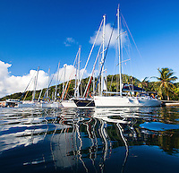 Yacht tied to dock in Raiatea with reflections in the water
