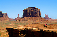 Horseback cowboy views Monument Valley, Utah with mittens. National Park, USA