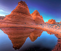 The teepees of Paw Hole at South Coyote Buttes are reflected in a nearby watering hole in Northern Arizona