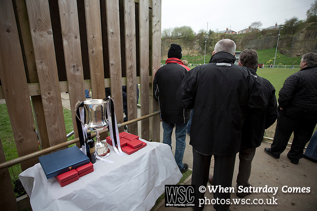 Cefn Druids AFC 1 Buckley Town 0, 12/04/2014. The Rock, Cymru Alliance league. Officials watching the action beside the league trophy at The Rock, Rhosymedre, home to Cefn Druids AFC, during the club's final home game of the season against Buckley Town (in yellow) in the Cymru Alliance league. Druids, reputedly the oldest football club in Wales, won the Alliance league the previous week and were awarded the trophy after the Buckley Town match, which they won by 1 goal to nil, watched by a crowd of 246. The Cymru Alliance was the second tier of Welsh football based in north and mid Wales, promotion from which led directly into the Welsh Premier League. Photo by Colin McPherson.