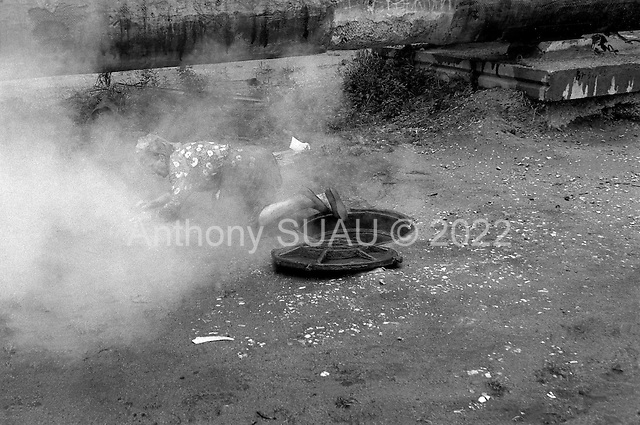 Moscow, Russia.1995.A pensioner crawls out of a steaming warm man hole into the cold air of Moscow.
