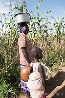 N. Uganda, Kitgum District. Peter C. Alderman Foundation project. A mother carrying a pot on her head with her children.The baby is covered with a gourd shell to protect it from the sun.