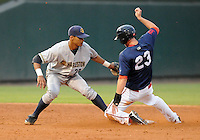 Shortstop Kelvin Castro (29) of the Charleston RiverDogs makes the tag on Jeremy Hazelbaker (23) of the Greenville Drive who is caught stealing in a game on Aug. 24, 2010, at Fluor Field at the West End in Greenville, S.C. Photo by: Tom Priddy/Four Seam Images