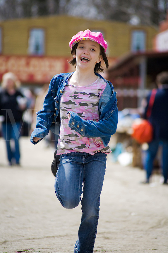 A young girl playfully running in the outdoors.