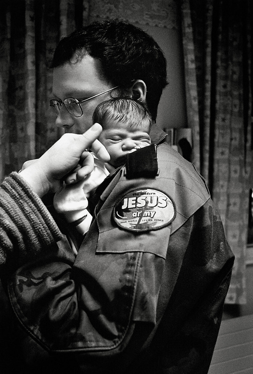 © John Angerson, Love Power Sacrifice (2007).<br /> Jesus Army elder Jack Sutcliffe watches over his newly born daughter, Grace, at the Leeds General infirmary intensive care baby unit.