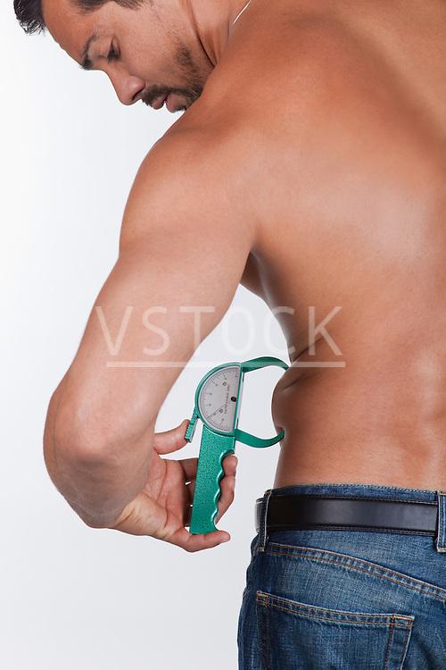 USA, California, Fairfax, Man measuring belly with caliper