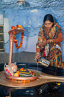 India, Dehradun.  Hindu Indian Woman Making an Offering to Sheshnag, the Divine Five-headed Serpent in Hindu Mythology, at Tapkeshwar Hindu Temple.