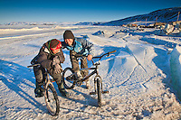 Two inuit boys on bicycles in the community of Arctic Bay near the north end of Baffin Island in Nunavut, Canada. This is the middle of May and it will still be several months before the ice will leave the inlet, so snowmobiles and komatik sleds are still the main source of transportation around the high arctic. No Releases. Editorial Use Only.