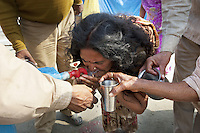 India. Uttar Pradesh state. Allahabad. Maha Kumbh Mela. An indian woman wearing a saree drinks water from a faucet into her two hands. The Kumbh Mela, believed to be the largest religious gathering is held every 12 years on the banks of the 'Sangam'- the confluence of the holy rivers Ganga, Yamuna and the mythical Saraswati. The belief is that bathing and taking a holy dip will wash and free one from all the past sins, get salvation and paves the way for Moksha (meaning liberation from the cycle of Life, Death and Rebirth). The Maha (great) Kumbh Mela, which comes after 12 Purna Kumbh Mela, or 144 years, is always held at Allahabad. Uttar Pradesh (abbreviated U.P.) is a state located in northern India. 10.02.13 © 2013 Didier Ruef