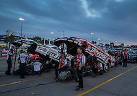 Apr. 5, 2013; Las Vegas, NV, USA: Crew members strap in NHRA funny car drivers Courtney Force (right) and father John Force in the staging lanes during qualifying for the Summitracing.com Nationals at the Strip at Las Vegas Motor Speedway. Mandatory Credit: Mark J. Rebilas-