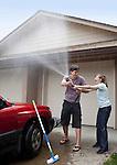 USA, Oregon, Ashland, young couple washing car in front of garage