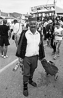 Festival di trombe e ottoni di Guca (Cacak). Un uomo vestito in abito tradizionale e con una borsa vende bottiglie di rakija (grappa) --- Trumpet festival of Guca (Cacak). A man dressed in traditional cloth and with a bag selling bottles of rakija (brandy)
