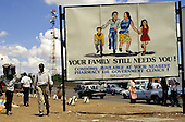 Lusaka, Zambia, Africa. Anti-Aids poster beside a busy road with telecommunications relay tower behind.