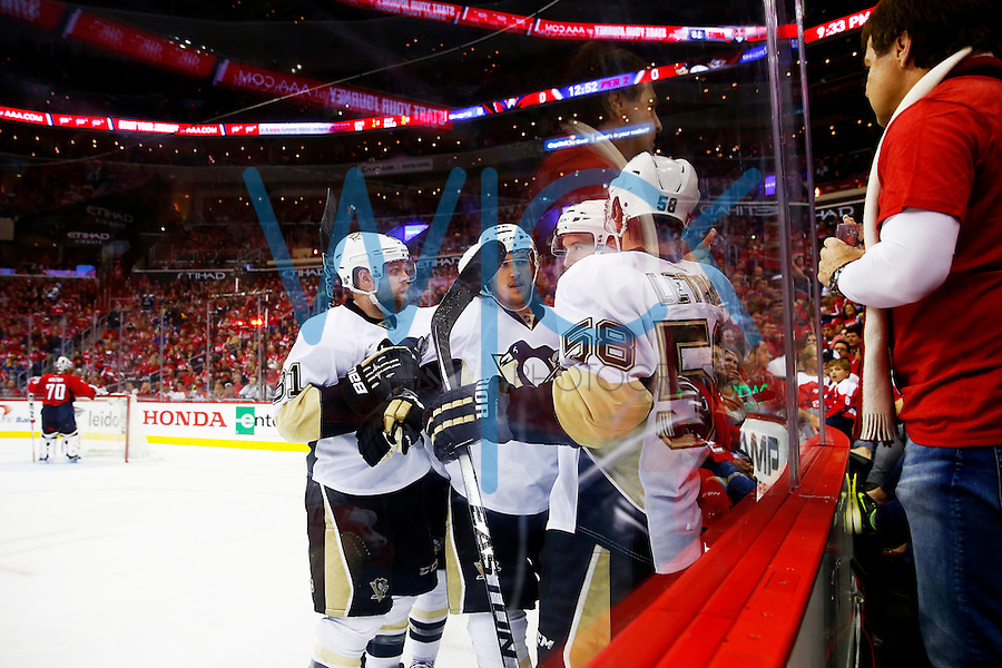 Carl Hagelin #62 of the Pittsburgh Penguins is congratulated by teammates following his goal in the second period against the Washington Capitals during game two of the second round of the Stanley Cup Playoffs at Verizon Center in Washington D.C. on April 30, 2016. (Photo by Jared Wickerham / DKPS)