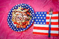 A 4th of July dessert with blue berries, strawberries ice cream, syrup.  Celebrate!