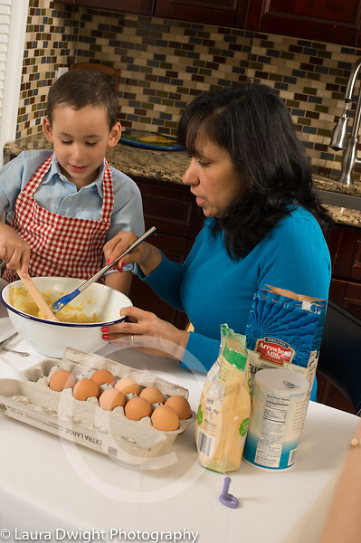 3 year old boy at home in kitchen learning to cook with mother, baking, stirring batter