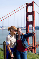 Tourists enjoying sunshine and taking portrait picture of Famous Landmark of San Francisco the Golden Gate Bridge and the bay and city behin