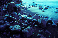Close up of a black sand beach with rocks
