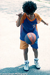6 year old girl bouncing basketball on pavement full length biracial African American and Caucasian