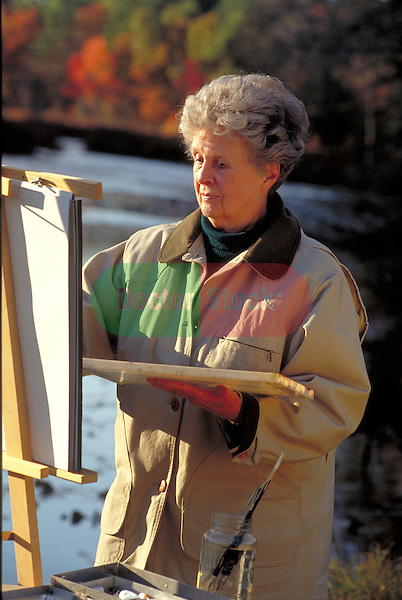 elder woman painting landscape outside