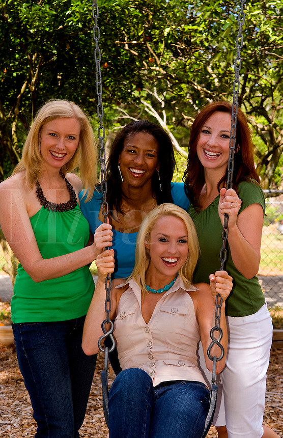 Four girlfriends of different ethnic backgrounds having fun and laughing on swing outdoors as friends