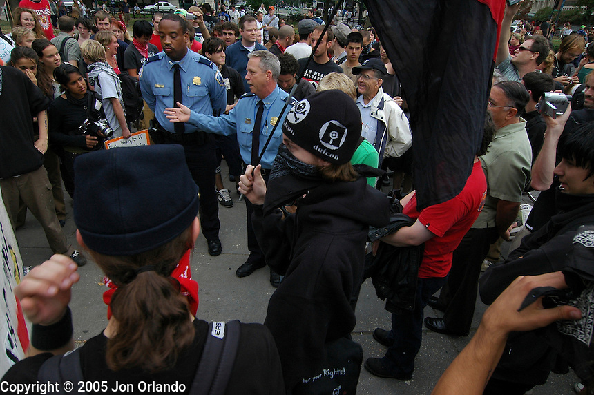 Anarchists and cops interact before an anti-war march begins in  Washington, DC in September 2005.
