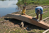 Xingu Indigenous Park, Mato Grosso State, Brazil. Aldeia Tuiarare (Kaiabi). Man carving a boat out of a solid tree trunk.