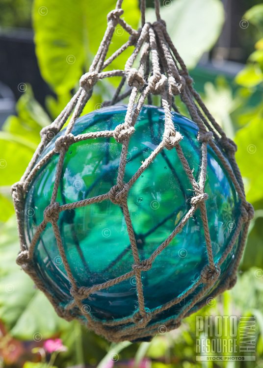 Blue green glass ball fishing float in a rope net covering
