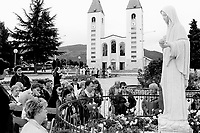 Bosnia. Medjugorje. Pilgrimage. Center of prayers. Shrine of the Queen of Peace, the Virgin Mary. Pilgrims pray in front of the Virgin Mary's statue. The church was consecrated on january 19 1969. Today it is the focal point of prayer life and place of gathering for the parishioners and pilgrims. The holy mass and the prayer programme take place in the church, or during the summer, at the exterior altar. © 2002 Didier Ruef .