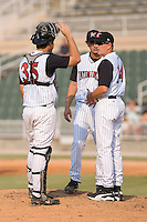 Kannapolis Intimidators pitching coach Larry Owens (14) has a chat on the mound with catcher John Curtis (35) and Miguel Socolovich (30) at Fieldcrest Cannon Stadium in Kannapolis, NC, Sunday August 10, 2008. (Photo by Brian Westerholt / Four Seam Images)