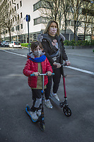 """Switzerland. Canton Ticino. Lugano. A woman and a child wear a mask on their faces to protect themselves from the Coronavirus (also called Covid-19). They are enjoying a short ride outside on a push scooter. Due to the spread of the coronavirus (also called Covid-19), the Federal Council has categorised the situation in the country as """"extraordinary"""". It has issued a recommendation to all citizens to stay at home, especially the sick and the elderly. The Federal Council (German: Bundesrat, French: Conseil fédéral, Italian: Consiglio federale, Romansh: Cussegl federal) is the seven-member executive council that constitutes the federal government of the Swiss Confederation. From March 16 the government ramped up its response to the widening pandemic, ordering the closure of bars, restaurants, sports facilities and cultural spaces. Only businesses providing essential goods to the population – such as grocery stores, bakeries and pharmacies – are to remain open. 21.03.2020 © 2020 Didier Ruef"""