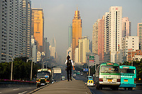 A woman walks along the central reservation of Shennan Road in Shenzhen, China. Shennan Road, stretching from east to west, is one of the busiest and most prosperous arteries in Shenzhen, and was selected as one of the top eight scenic spots of Shenzhen for its appealing views of sophisticated landscapes, landmark buildings and colorful lighting. .15 May 2007