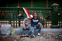 Two anti government protesters resting on Tahrir Square. Throughout Friday, 4 February, anti government protesters protected their positions from pro Mubarak supporters around Tahrir square, the scene of heavy clashes between pro and anti government protesters. Continued anti-government protests take place in Cairo calling for President Mubarak to stand down. After dissolving the government and allowing for talks with opposition parties Mubarak still refuses to step down from power...