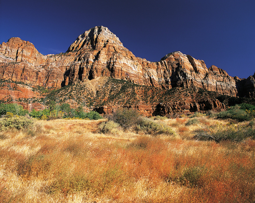 Rock peaks at the entrance to Zion Canyon, with red rock-faces and blue sky behind. Zion, Utah, US