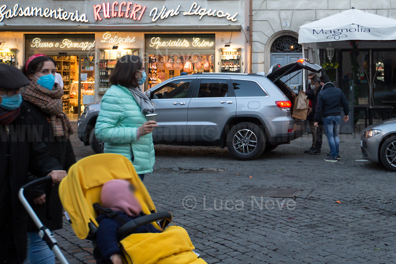 Minister doing food shopping.<br /> <br /> Campo de' Fiori.<br /> <br /> Rome, Italy. 17th Mar, 2021. Documenting Rome from a Bus window (Number 81) and during a quick walk in the City center, while the new and tougher Covid-19 restrictions, imposed by Mario Draghi's Government, have been implemented since Monday morning in Rome, its surrounding Lazio Region, and other 9 Regions, including: Lombardia, Campania, Molise, Emilia Romagna, Friuli-Venezia Giulia, Marche, Piemonte, Puglia, Veneto and Autonomous Province of Trento. The local authorities tightened rules and restrictions due to a spike in the Covid-19 / Coronavirus cases. A new self-certification (autocertificazione, downloadable from here 1.) is needed to leave home which is allowed only for urgent reasons, mainly work and health. Italy will be placed under nationwide lockdown over the Easter weekend. <br /> <br /> Footnotes & Links:<br /> 1. http://www.regione.lazio.it/binary/rl_main/tbl_news/autocertificazione_1_.pdf