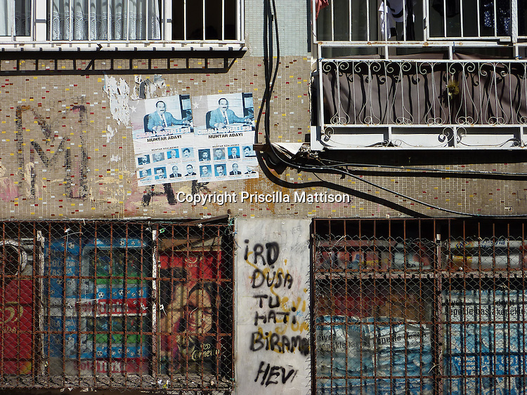 Istanbul, Turkey - September 23, 2009:  A building facade is covered with mosaic tiles, window bars, graffiti, posters, and electric wires.