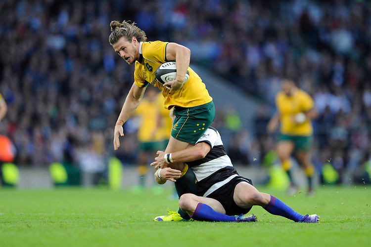 Rob Horne of Australia is tackled during the Killik Cup match between Barbarians and Australia at Twickenham Stadium on Saturday 1st November 2014 (Photo by Rob Munro)