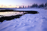 Snow-covered shore around a tide pool at Acadia National Park, Maine, USA