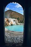 The green waters of the Garm-Chashma hot springs in the Ishkashim District of Tajikistan mountains are framed in a doorway.