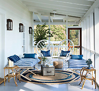 The sun room is transformed into a sleeping porch. A pair of cots, outfitted with gauzy throw beds from Hable Construction, and the Chippendale style peacock chairs are painted rattan. The abaca rug is by Jaipur, and the floor is painted Adagio by Benjamin Moore. 9. The cots can be folded away and the space doubles as a cosy lounge.