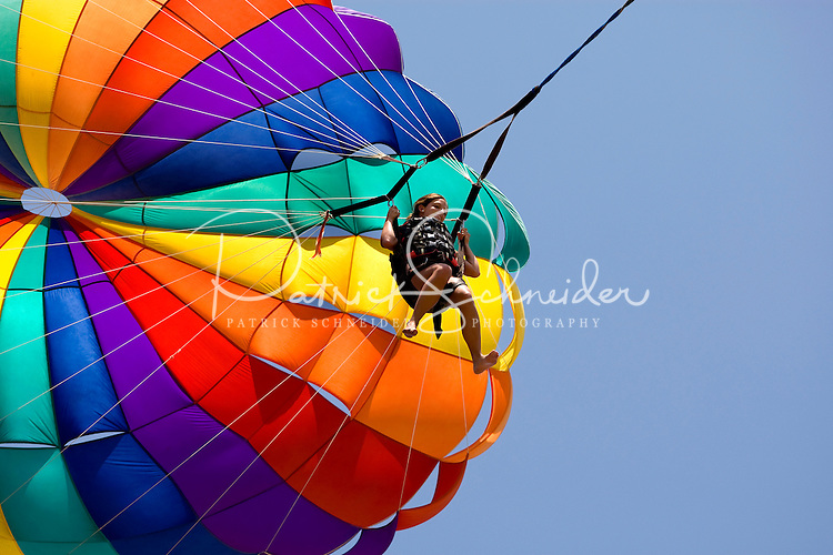 A woman parasails beneath a rainbow colored parasail over Playa la Ropa Beach in Zihuatanejo, Mexico. Zihuatanejo is the twin sister town of Ixtapa. (taken August 2007). Photo by Patrick Schneider Photo.com