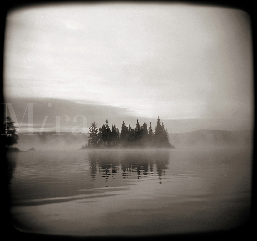 Mist rising from a lake around an island in Algonquin Provincial Park in Ontario, Canada.