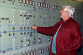 Pocerady, Czech Republic. Power station; man in overalls at control station.