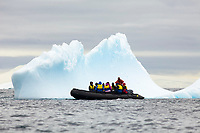 Iceberg grounded in shallow bay with tourists in inflatable boat. Antarctica Dallman Bay, Gerlache Strait and Schollaert Channel, Palmer Archipelago, Southern Ocean